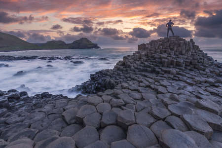 Silhouette of one person standing at Giant Causeway rocks at sunset in Northern Ireland Reklamní fotografie