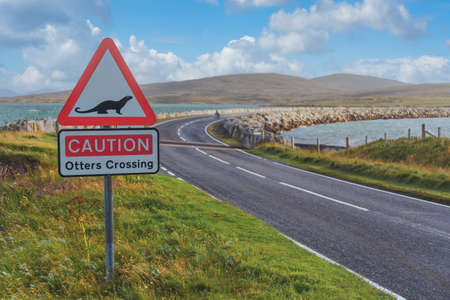 Caution Otters Crossing red triangle road sign by causeway, North Uist Outer Hebrides Western Isles Scotland UK Britain