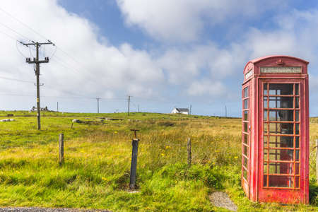 Red telephone box and crofters houses at North Uist, Outer Hebrides, Scotland