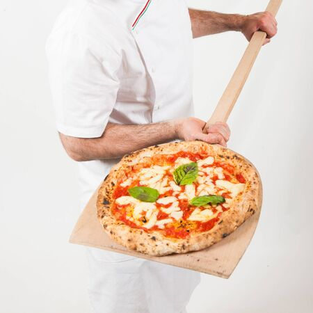 real italian pizza margherita with mozzarella cheese, tomatoes, basilico resting on the pizza maker wooden shovel, from the top, white background