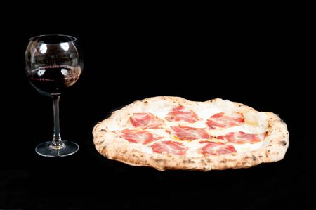 real italian pizza margherita with pork loin mozzarella cheese, in a black background from the top whit a glass of delicious Italian  red Chianti wine  Stock fotó