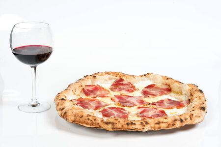 real italian pizza margherita with pork loin mozzarella cheese, in a white background whit a glass of delicious Italian red Chianti wine
