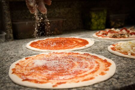 the pizza maker prepares an Italian pizza by putting the Parmesan on the tomato sauce