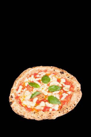 real italian pizza margherita with mozzarella cheese, tomatoes, basilico in a black background from the top vertical with copy space