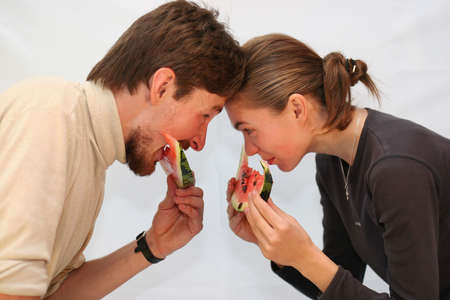 Young man and the woman eat a watermelon on white Stock Photo