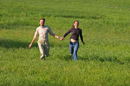 Young man and the woman run on a field Stock Photo