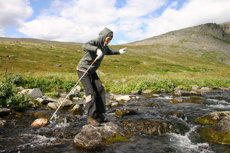 consternation: The girl fords the river in mountains