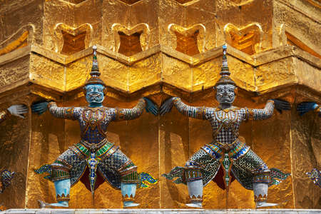 Statues surrounding a gold Thai pagoda Stock Photo