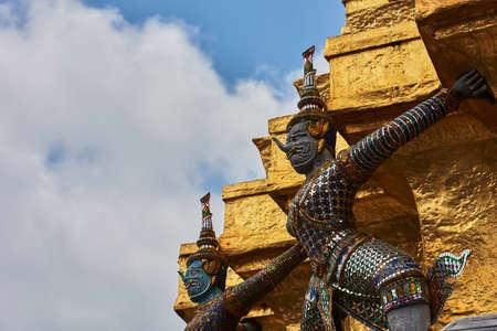 Statue surrounding a gold Thai pagoda