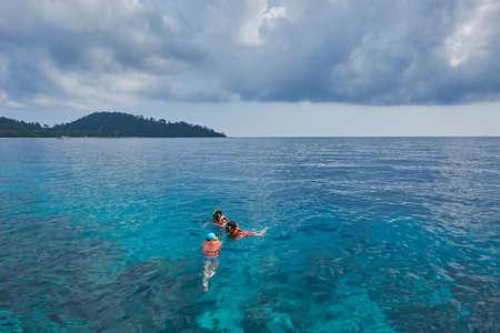 Three people snorkeling in the sea Stock Photo