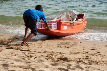 Boy pushing a boat into the sea