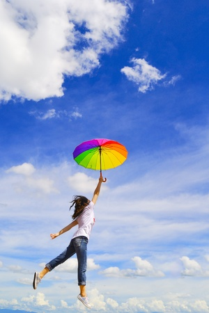 Multicolor umbrella woman jump to sky on beautiful day