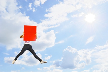 sun sky: Woman holding red blank board jumping and sun sky Stock Photo