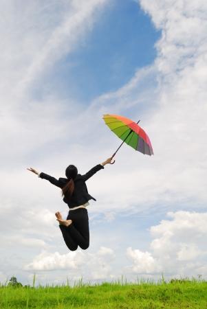 brincando: Mujer de negocios paraguas de saltar al cielo azul en los prados con paraguas rojo