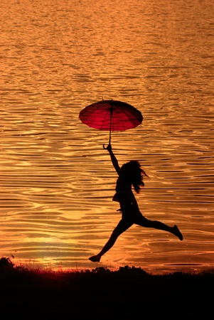 Umbrella woman jumping and sunset silhouette in Lake  photo