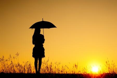 lluvia paraguas: Paraguas mujer y la silueta puesta de sol en el lago Foto de archivo