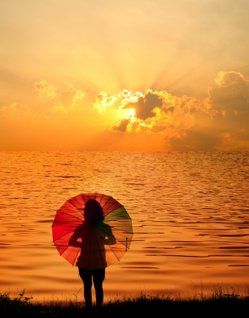 Umbrella woman and sunset silhouette in Lake photo