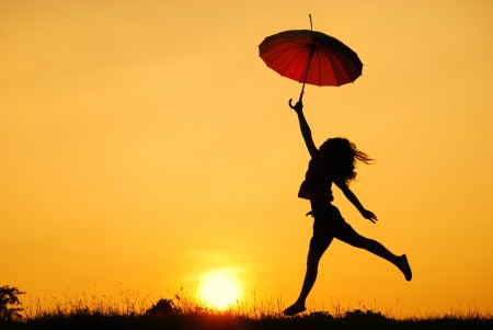 Umbrella woman jumping and sunset silhouette in Lake  Foto de archivo