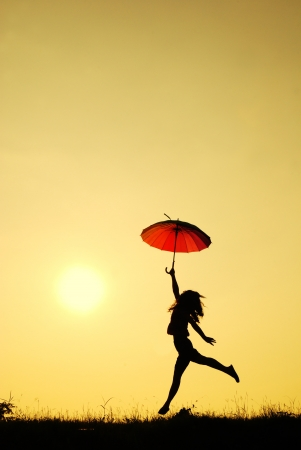 lluvia paraguas: Paraguas saltar la mujer y la silueta puesta de sol en el lago