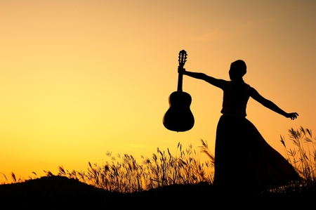 happiness people silhouette on the sunset: Woman and guitar with sunset silhouette