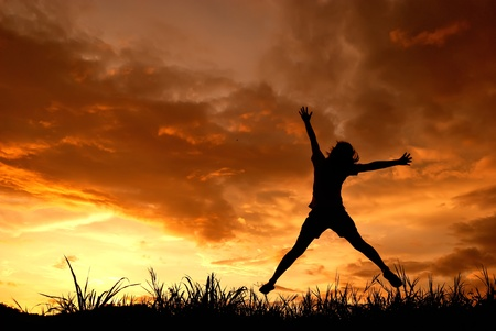 Jumping woman and sunset silhouette  photo