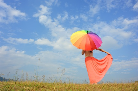 Woman holding multicolored umbrella against the sunny sk  photo