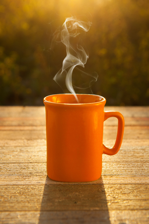 mug of coffee: hot coffee on wood table in sunset in the moring