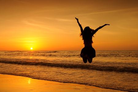 puesta de sol: Feliz mujer que salta en el mar Puesta de sol Foto de archivo