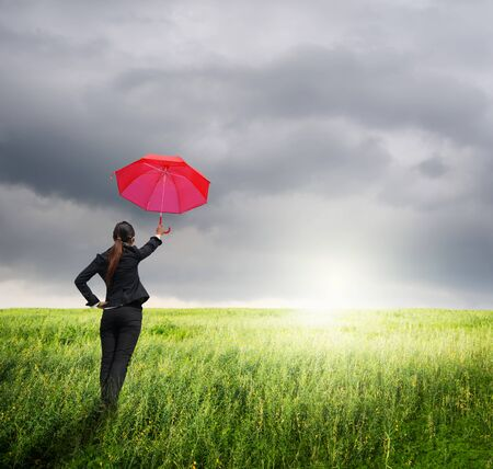 rainclouds: Business umbrella woman standing to rainclouds in grassland with red umbrella