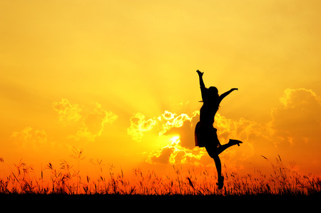 Woman jump and sunset silhouette when she happy