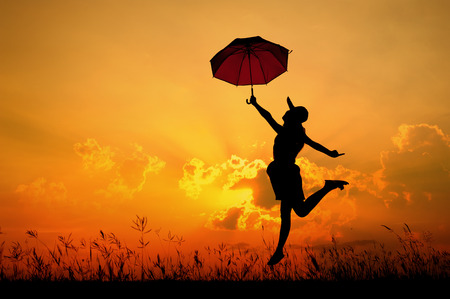 Umbrella woman jump and sunset silhouette when she happy