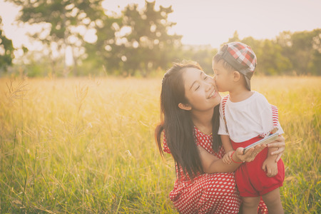 happy family. A mother and son kissing in grass fields outdoors at evening.Vintage Tone and copy space Foto de archivo
