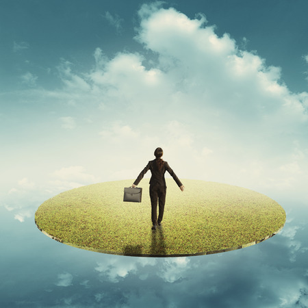 woman holding bag: Relax business woman holding bag in floating grass land over the sky Stock Photo