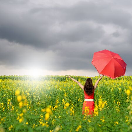 rainclouds: Woman holding red umbrella in Yellow flower field and Rainclouds Stock Photo