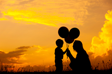 Silhouette of A mother and son playing outdoors at sunset