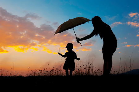 Silhouette of a mother and son holding umbrella and playing outdoors at sunset silhouette Archivio Fotografico