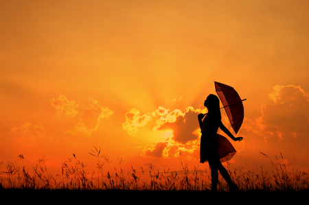 Umbrella woman standing and sunset silhouette