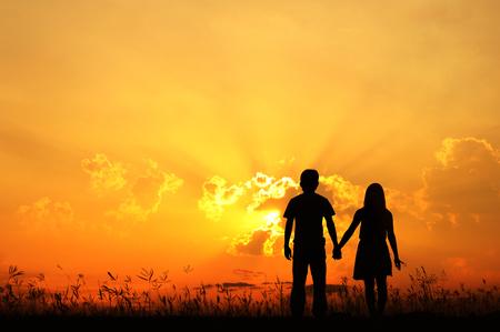 niño parado: El hombre y la silueta de la mujer el amor en la puesta del sol