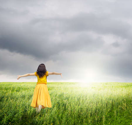 rainclouds: Relax Woman in green fields with rainclouds Stock Photo
