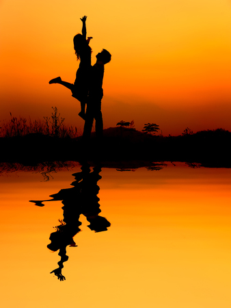 femme amoureuse: Reflection of Man and Woman love silhouette in sunset Banque d'images
