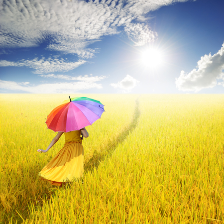 Relax woman holding multicolored umbrella in Yellow rice field and cloud sky