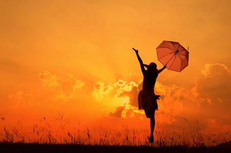 mujeres felices: Mujer saltando Paraguas y la silueta puesta de sol Foto de archivo