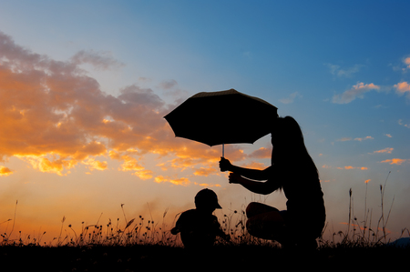 Silhouette of a mother and son holding umbrella and playing outdoors at sunset Foto de archivo