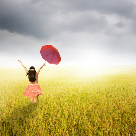 rainclouds: Beautiful woman holding red umbrella in rice field and rainclouds Stock Photo