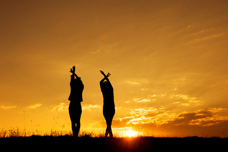 Relax of two women standing and sunset silhouette with copy space.