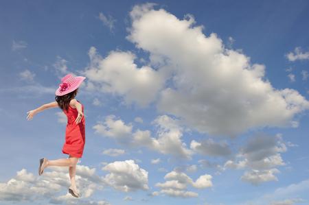Happy woman jumping to blue cloud sky. Foto de archivo