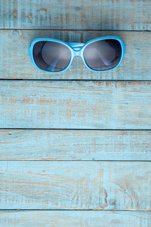 Sunglasses on blue wood.Summer holiday background concept