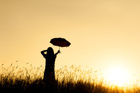 Umbrella woman stand and sunset silhouette with copy space. Foto de archivo