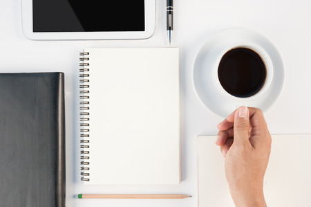 Man hand holding Cup of hot coffee, tablet, phone and notebook on white background