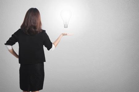Asia Business woman holding idea bulb on wall background Foto de archivo